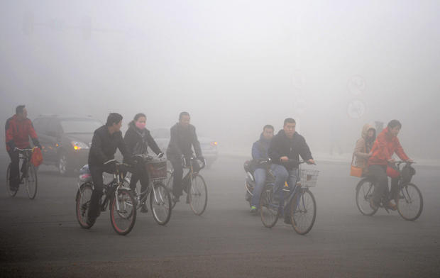 Cyclists ride along a road as heavy fog engulfs Daqing, China.