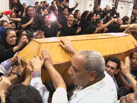 Mourners grieve for five Christians killed by masked gunmen.