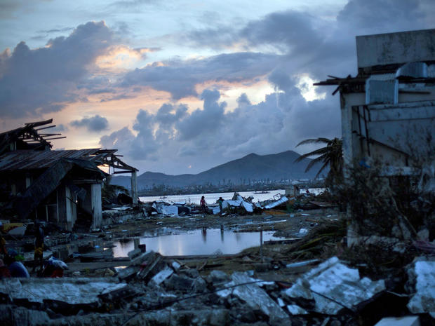 Typhoon Haiyan survivors walk through the ruins of their neighborhood on the outskirts of Tacloban, Philippines, Nov. 13, 2013.