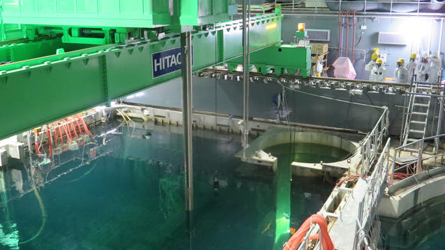 Workers remove nuclear fuel rods from a pool at No. 4 reactor of the Fukushima Daiichi Nuclear Power Plant