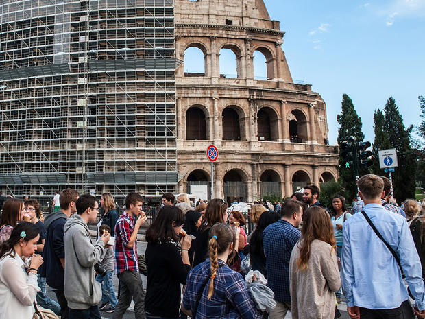 Tourists and locals walk in front of the Colosseum, partially covered in scaffolding weeks before restoration work began, Oct. 9, 2013 in Rome