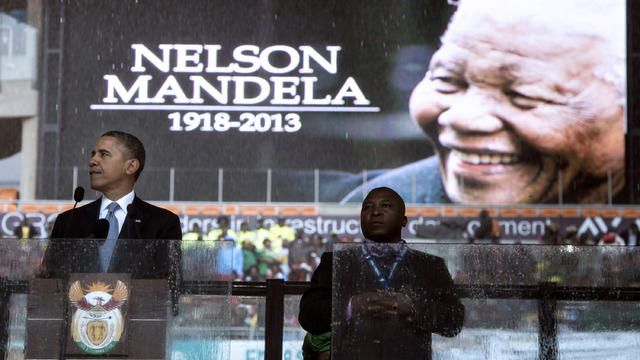 President Obama pauses while speaking during the memorial service for late South African President Nelson Mandela