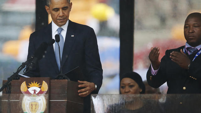 President Obama looks down as he stands next to a sign-language interpreter as he makes his speech at the memorial service for former South African President Nelson Mandela at FNB Stadium in Soweto near Johannesburg Dec. 10, 2013.