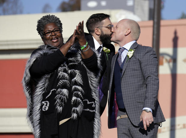 Aubrey Loots, right, and Danny Leclair, the first gay couple to be married aboard a float in the Tournament of Roses, kiss after being wed by the Rev. Alfreda Lanoix of the Unity Fellowship Church of Christ, left, aboard the AIDS Healthcare Foundation float in the 125th Rose Parade in Pasadena, Calif., Jan. 1, 2014.