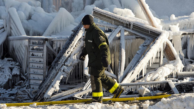 A police investigator looks over the frozen rubble after a fire destroyed a seniors residence in L'Isle-Verte, Quebec, Jan. 23, 2014.