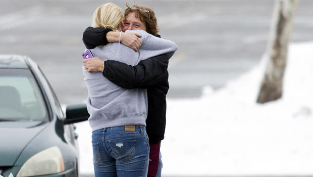 Two people embrace in the parking lot at the scene of a shooting at The Mall in Columbia Jan. 25, 2014, in Columbia, Md.
