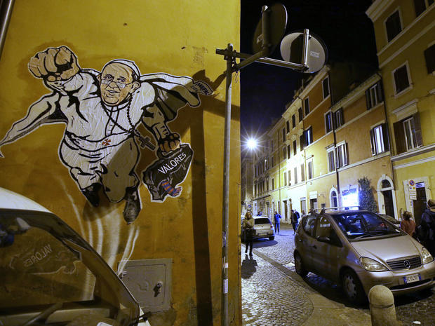 """Graffiti depicting Pope Francis as a Superman-like hero, clutching a bag with the Spanish word for """"Values,"""" is seen on a wall of the Borgo Pio district near St. Peter's Square"""