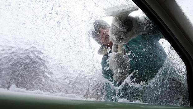 Terry Gillis scrapes ice off his car's window Feb. 12, 2014, in Fort Payne, Ala.