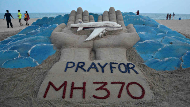 Beachgoers walk past a sand sculpture made by Indian sand artist Sudersan Pattnaik with a message of prayers for the missing Malaysian Airlines Flight MH370 at Puri beach in India March 12, 2014.