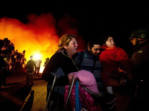 People flee to safety after a wildfire reactivated in Valparaiso