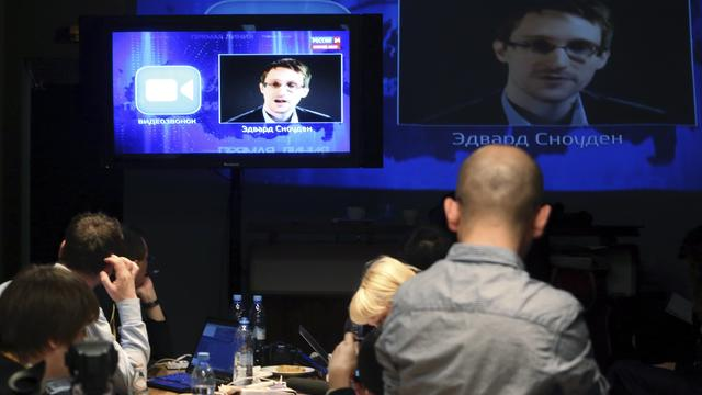 Journalists listen to a question posed by former NSA contractor Edward Snowden, at a media center during Russian President Vladimir Putin's live broadcast