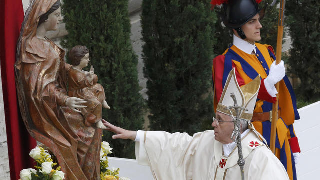 Pope Francis touches the statue of the Virgin Mary as he arrives for the canonization ceremony of Popes John XXIII and John Paul II in St. Peter's Square