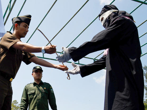 A government prosecutor hands over a whip to the executioner before a public caning in Aceh