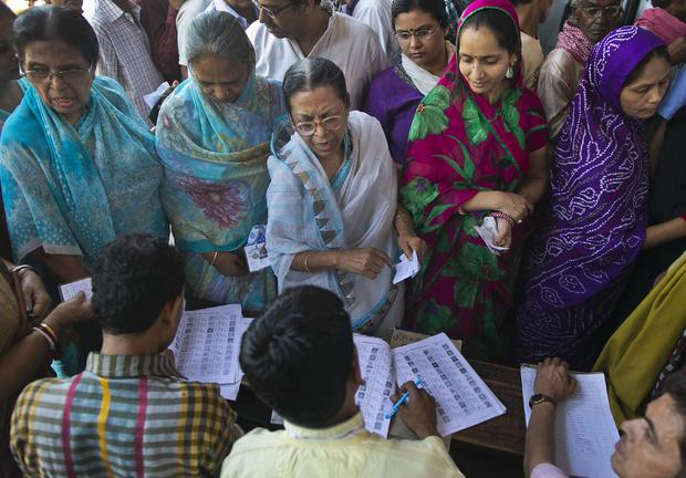 Voters get their names checked in a voter's lists at a polling station during the final phase of the general election in Varanasi