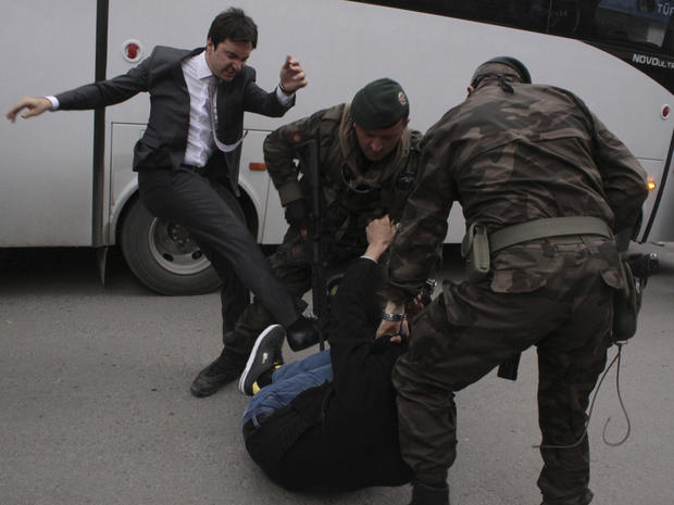 A protester is kicked by Yusuf Yerkel (L), advisor to Turkey's Prime Minister Tayyip Erdogan, as Special Forces police officers detain him during a protest against Erdogan's visit to Soma, a district in Turkey's western province of Manisa