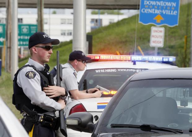 Armed Royal Canadian Mounted Police (RCMP) officers guard exit ramp during hunt for Justin Bourque, who allegedly shot 3 police officers dead and wounded 2 more in Moncton