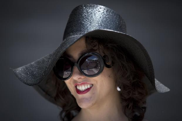 Leah Heather poses for a portrait with her hat before the 146th running of the 2014 Belmont Stakes in Elmont, New York, June 7, 2014.
