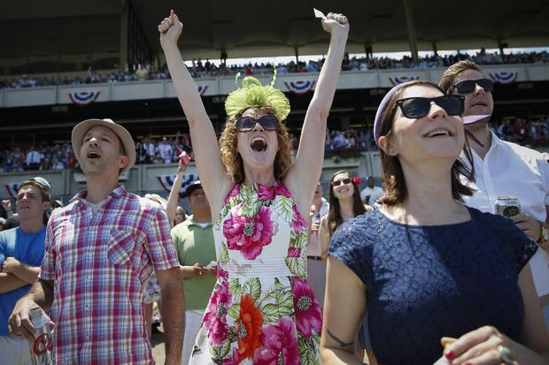 Shayna Reade, center, cheers as horses cross the finish line during the third race at Belmont Park before the 2014 Belmont Stakes in Elmont, New York, June 7, 2014.