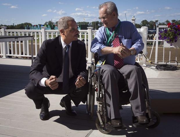 Attorney General Eric Holder, left, kneels down to speak with former jockey Ron Turcotte before the 146th running of the 2014 Belmont Stakes in Elmont, New York, June 7, 2014.  Turcotte rode famed horse Secretariat to the Triple Crown and Holder was sitti