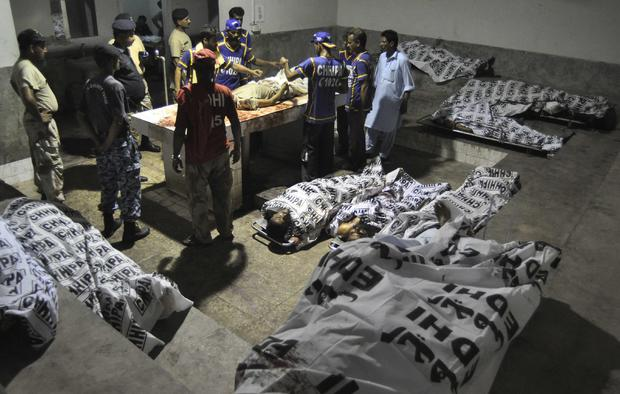 Rescue workers and paramilitary soldiers gather next to bodies after an attack on Jinnah International Airport, at a hospital morgue in Karachi