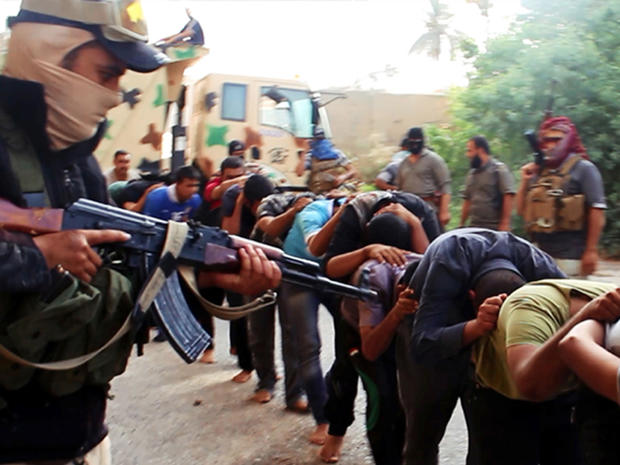 This image posted on a militant website June 14, 2014, which has been verified appears to show militants from the al-Qaeda-inspired Islamic State of Iraq and Syria (ISIS) leading away captured Iraqi soldiers dressed in plain clothes after taking over a ba