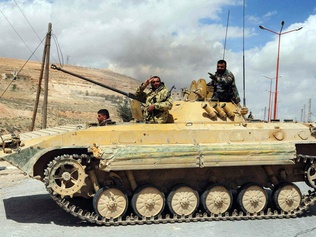 Syrian soldiers flash the sign for victory as they drive a tank in al-Sarkha village in the Qalamun mountains, northeast of Damascus, after taking control of the village from rebel fighters April 14, 2014.
