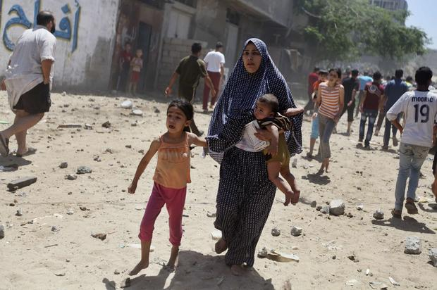A Palestinian woman runs with her children following what police said was an Israeli airstrike