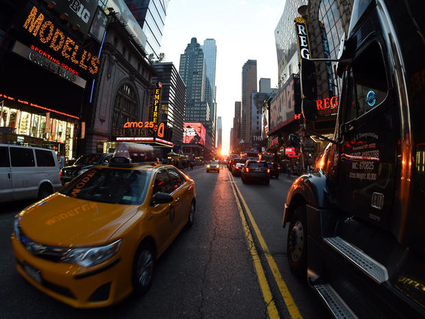 Traffic slows as tourists and pedestrians watch the Manhattanhenge phenomenon July 11, 2014 on 42nd Street in New York.