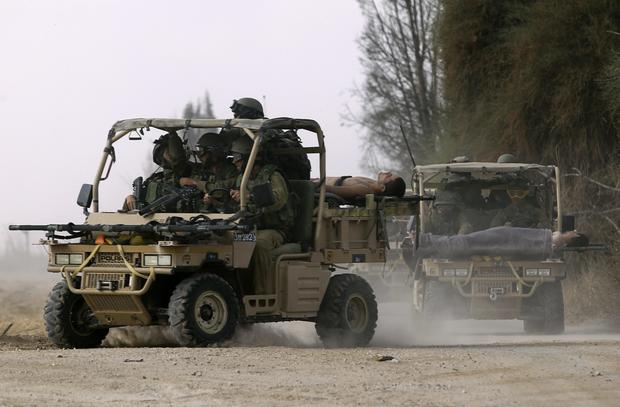 Israeli soldiers, wounded during an offensive in Gaza, are evacuated near the border with the central Gaza Strip