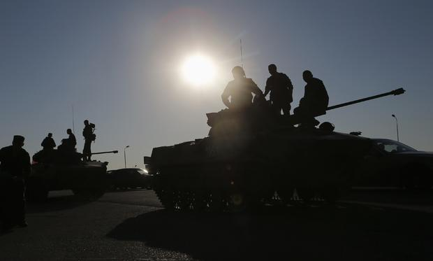 Russian military personnel sit atop armoured vehicles outside Kamensk-Shakhtinsky, in Russia's Rostov region
