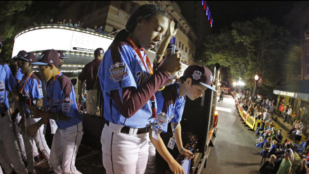 Mo'ne Davis, center, a member of the Taney Little League team from Philadelphia, signs baseballs as she and her teammates ride in the Little League Grand Slam Parade as it makes its way through downtown Williamsport, Pa., Aug. 13, 2014.