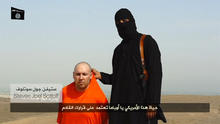 A masked Islamic State of Iraq and Syria militant speaks next to a man purported to be U.S. journalist Steven Sotloff at an unknown location in this still image from an undated video posted on a social media website.