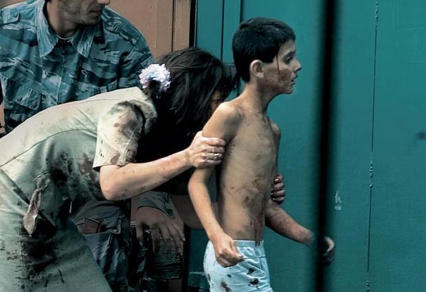 Teacher Elena Kosumova runs to safety with her son, Timor.