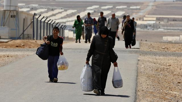 Newly-arrived Syrian refugees carry their belongings as they walk at Azraq refugee camp near Al Azraq area, east of Amman, Jordan, on August 19, 2014
