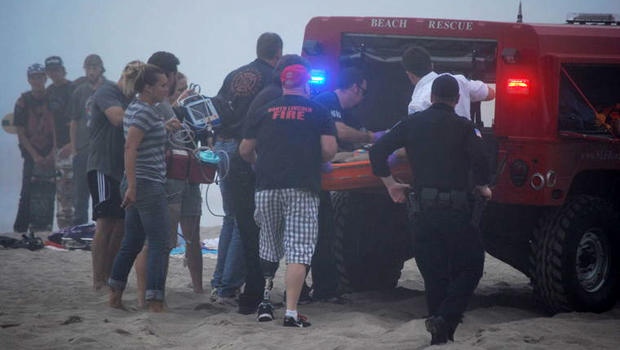 A 9-year-old girl who was trapped beneath the sand when a sand cave collapsed is put into an ambulance in Lincoln City, Ore., Aug. 29, 2014.