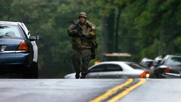 A member of the Pennsylvania State Trooper's Tactical Response Unit walks along Route 402 Sept. 13, 2014, near the scene where a Pennsylvania state trooper was killed and another trooper was injured during a shooting the previous night at the Pennsylvani