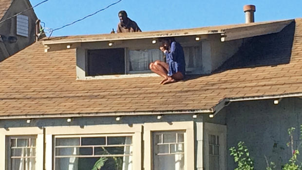 Melora Rivera, who fled her house through an attic window to escape an intruder, seen on the roof behind her, waits for help after an early-morning break in at her house in the Venice neighborhood of Los Angeles, Sept. 24, 2014.
