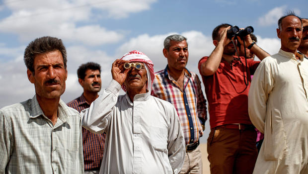 Two Kurdish men look through binoculars as Kurdish people from the region gather next to the borderfence in Suruc, Turkey, Sept. 27, 2014, to see the fighting between the Islamic State of Iraq and Syria and Kurdish Peshmergas.