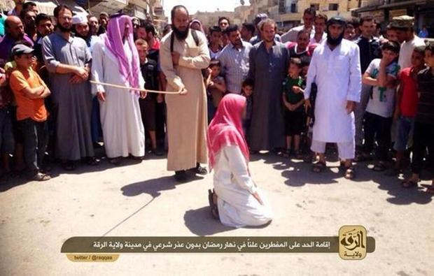 A member of ISIS' religious police flogs a man found guilty of violating Islamic law by breaking the fast for the Muslim holy month of Ramadan in the Syrian city of Raqqa
