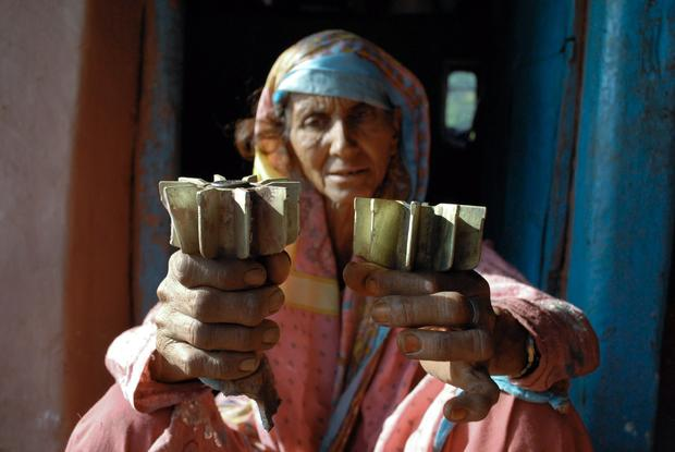 Woman holds mortar shell that damaged her village.