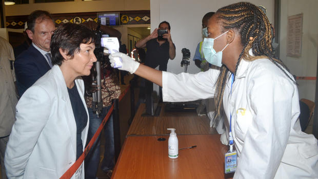A health employee takes the temperature of France official Annick Girardin, left, during a health inspection upon her arrival at the airport in the Guinean capital of Conakry Sept. 13, 2014.