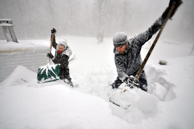 Tami Normile and Richard Brooks attempt to remove some of the five feet of snow from a rooftop Nov. 20, 2014, in the Lakeview neighborhood of Buffalo, N.Y.