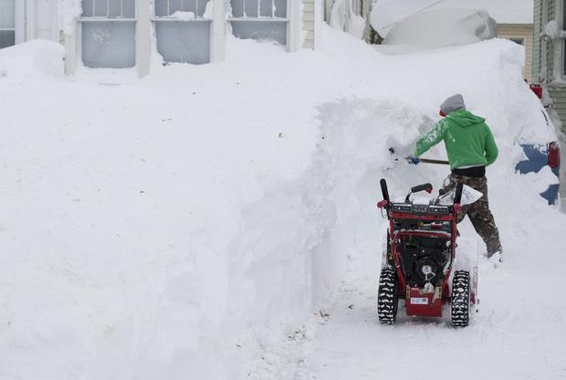 A man works to clear snow covering his vehicle following a storm in Buffalo, N.Y., Nov. 20, 2014.