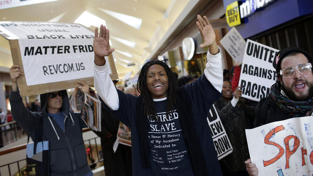 Demonstrators protesting the shooting death of Michael Brown hold signs as they walk through the Saint Louis Galleria mall yelling chants on Black Friday, Nov. 28, 2014, in St. Louis, Missouri.