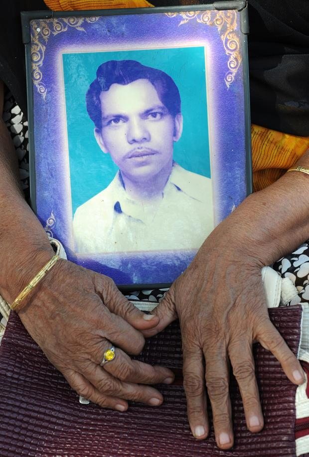 Bhopal gas disaster survivor Chironjee Bai Thakur holds a photograph of her late husband, Maharja Singh, during a protest rally in Bhopal Dec. 2, 2014.