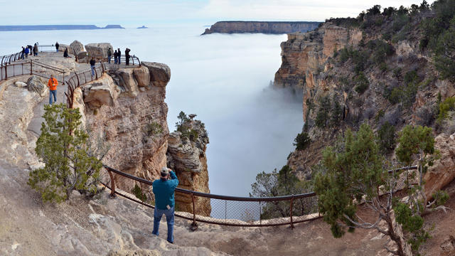 Visitors to Mather Point on the South Rim of Grand Canyon National Park, Ariz., view a rare weather phenomenon - a sea of thick clouds filling the canyon just below the rim, Dec. 11, 2014.