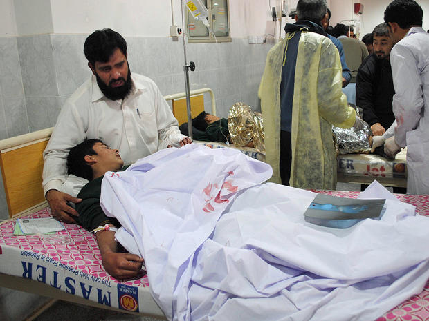 A man comforts his son, who was injured during an attack by Taliban gunmen on the Army Public School, at Lady Reading Hospital in Peshawar