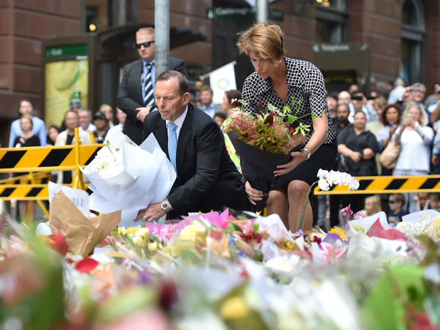 Australian Prime Minister Tony Abbott and his wife Margaret lay wreaths at a makeshift memorial near the site of fatal siege in the heart of Sydney's financial district, Dec. 16, 2014.