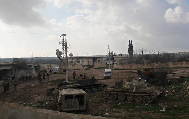 Islamic fighters walk around al-Hamidiyeh base, one of two military posts they took control of from the Syrian Army, Dec, 15, 2014.