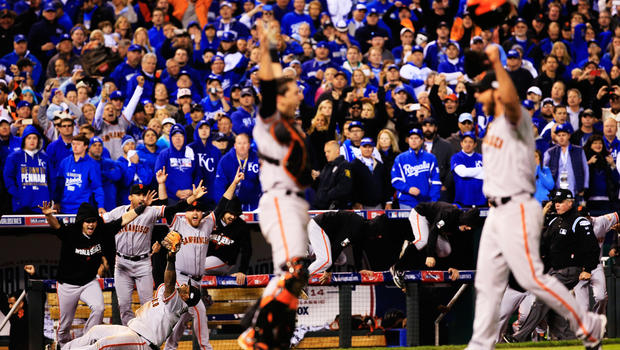 Buster Posey #28, Madison Bumgarner #40, Pablo Sandoval #48 and San Francisco Giants celebrate after beating Kansas City Royals to win Game Seven of 2014 World Series by score of 3-2 at Kauffman Stadium on Oct. 29, 2014 in Kansas City, Mo.